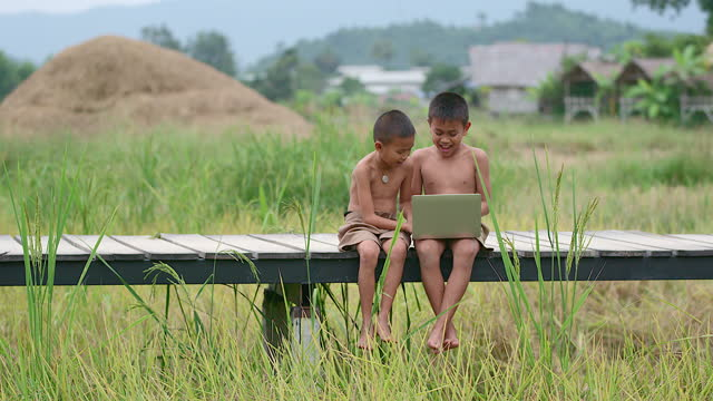 Two rural boys playing with a notebook happily. On a smiling face On a wooden bridge With a background in a field Means of access, The arrival of technology In the wilderness Can still use the internet. Two rural boys playing with a notebook happily. On a smiling face On a wooden bridge With a background in a field Means of access, The arrival of technology In the wilderness Can still use the internet. developing countries stock videos & royalty-free footage