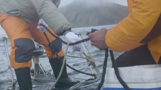 2 つの船乗りの男作業と結び目海船のボード上のロープに - 結ぶ点の映像素材/bロール