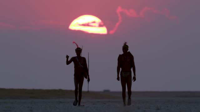 zwei san-buschmänner zu fuß aross der makgadikgadi pfannen mit den sonnenuntergang am roten himmel dahinter, botswana - stamm stock-videos und b-roll-filmmaterial