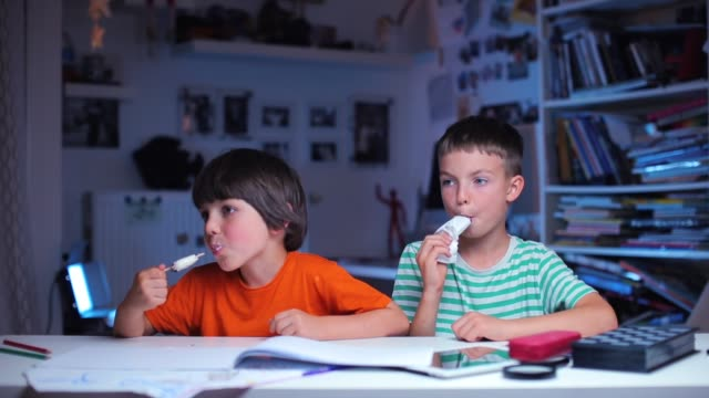 two schoolchildren eat ice cream while sitting at a table