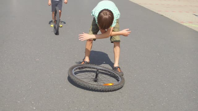 two schoolchildren play with wheels from a bicycle
