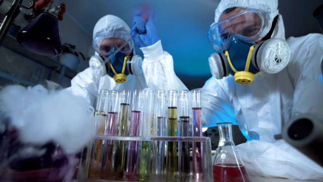 Two scientists in full biohazard masks video