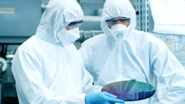 two scientists/ technicians in sterile suits check semiconductor silicon wafer that reflects many different colors, it will be made into computer chips. they work in a modern semiconductor fabrication plant. - chip komputerowy filmów i materiałów b-roll