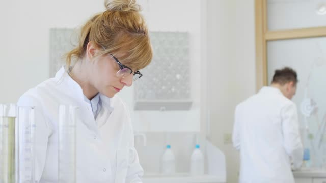 Two scientists working with terpene crystals and tablet in laboratory Scientists working with terpene crystals called terposolate. They are in pharmaceutical laboratory and CBD and CBDa oils are on table in glass tubes and erlenmeyer flasks. cbd oil stock videos & royalty-free footage