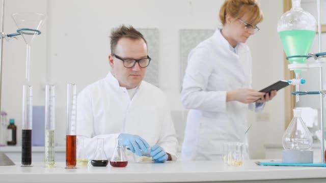 실험실에서 테르펜 결정과 태블릿으로 작업하는 두 과학자 - 칸나비디올 스톡 비디오 및 b-롤 화면