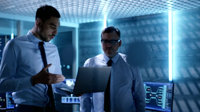 two security engineers walking in system control center. they have discussion, one of them holds laptop. room is full of working displays. - supporto tecnico video stock e b–roll