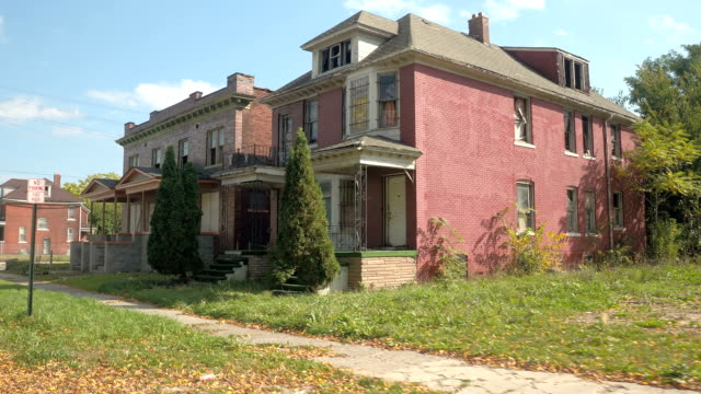 CLOSE UP: Two semi-detached abandoned decaying houses in Detroit CLOSE UP: Driving past two semi-detached brick-built abandoned decaying houses with broken windows after being robbed. Derelict crumbling building in ghetto. Ruined deserted homes in Detroit, USA poverty stock videos & royalty-free footage
