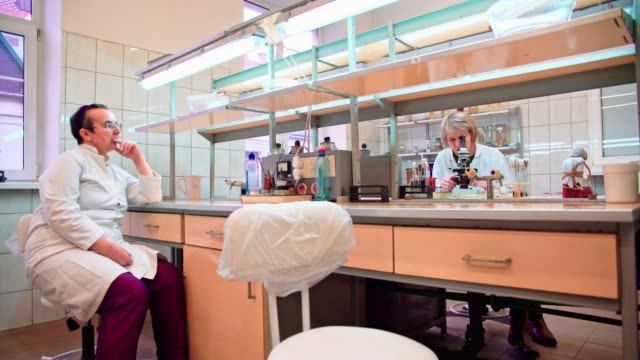 Two senior 50-years-old women, scientists, working together with the microscope and bacterial culture in the college microbiology lab video