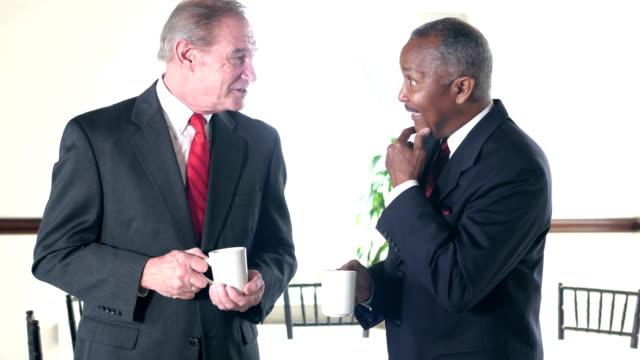 Two senior businessmen talking, having coffee video