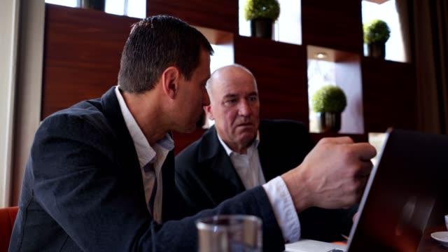 vídeos y material grabado en eventos de stock de dos empresarios de alto rango que trabajan en un café - comercio electrónico