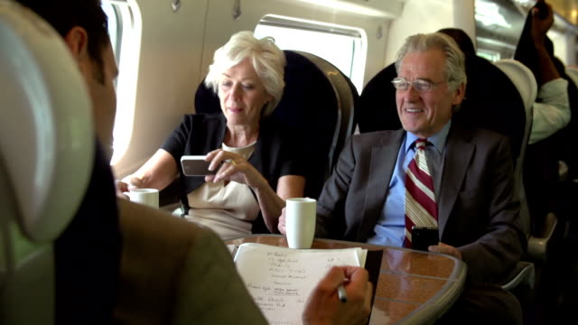 Two Senior Businesspeople Commuting On Train video