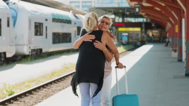 två seniora vänner möter varandra på tågstationen - aktiva pensionärer utflykt bildbanksvideor och videomaterial från bakom kulisserna