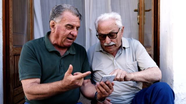 two senior friends using smartphone - mostrare video stock e b–roll