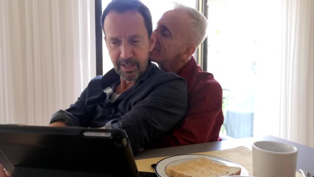 Two senior gay men being affectionate while looking at media on a tablet 4k video