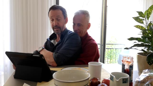 Two senior gay men being hugging as they look at media on a tablet 4k video