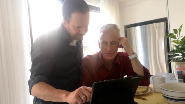 Two senior gay men discussing media on a tablet 4k video