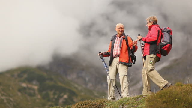 two senior hikers looking into distance video
