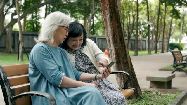 スマートフォンを使用している2人の年配の女性 - ベンチ点の映像素材/bロール