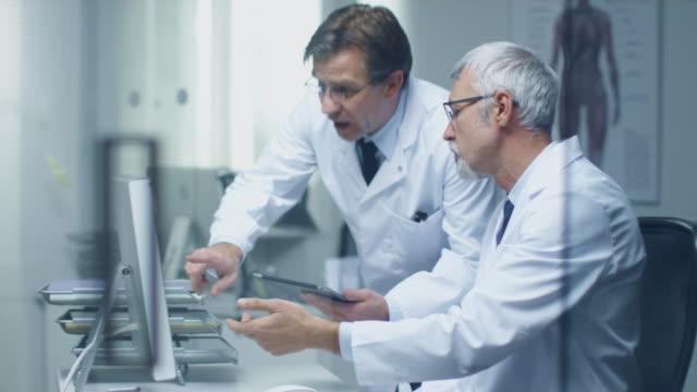 Zwei leitende Ärzte medizinische diskutieren über Desktop-Computer. Einer von ihnen halten Tablet-Computer. Büro ist Modern und hell. – Video