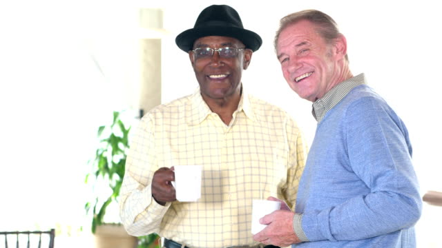 Two senior men conversing, drinking coffee video