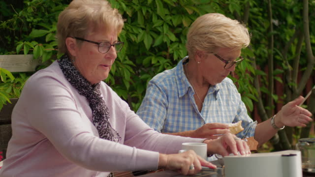 two senior retired pensioners having coffee and cake in the garden