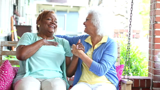 two senior woman talking, laughing on front porch - vicino video stock e b–roll