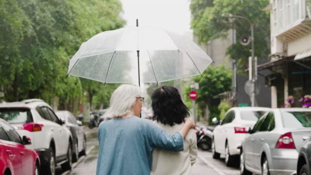 vídeos de stock e filmes b-roll de two senior women are on a walk in the city on a rainy day - guarda chuva