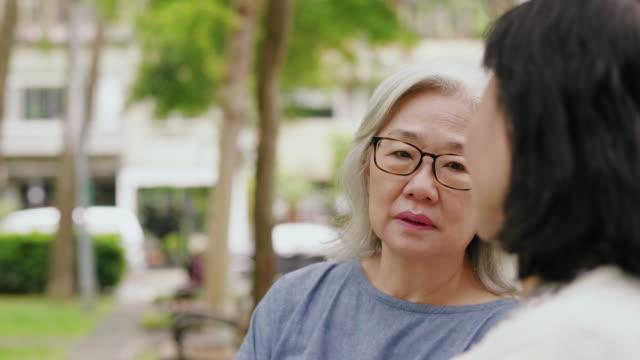 vídeos de stock, filmes e b-roll de duas mulheres sênior estão falando e passar o tempo junto em um parque público - amizade feminina