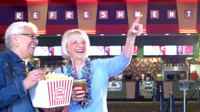 Two senior women at movie theater concession stand