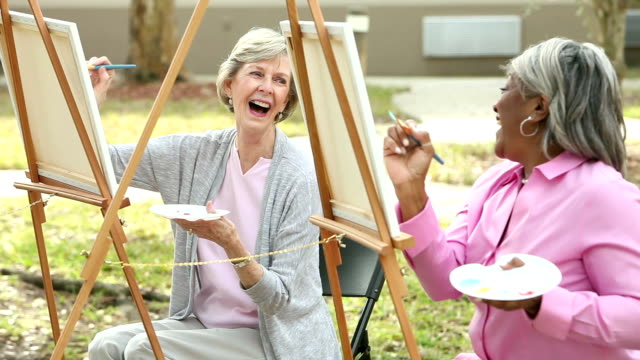 Two senior women chatting while painting on canvas video