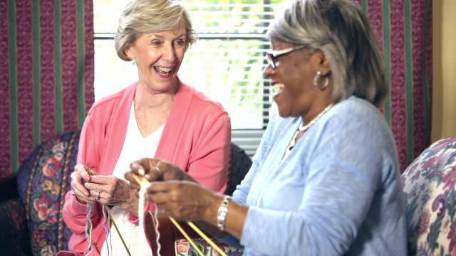 Two senior women knitting, chatting video
