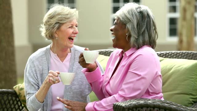 パティオ、コーヒーを飲みながら話に 2 人のシニア女性 - パティオ点の映像素材/bロール
