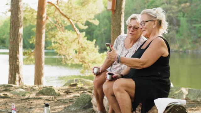 Två seniora kvinnor som använder Smart telefon på picknick i svensk skog video