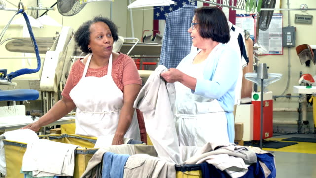Two senior women working at dry cleaners Two multi-ethnic senior women working together at a dry cleaners, conversing while they take laundry out of carts. They are in their 60s. The one wearing eyeglasses is Hispanic and her coworker is African-American. laundry basket stock videos & royalty-free footage