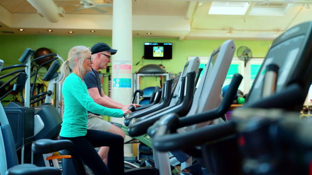 Two seniors, man, and woman doing together a fitness workout on a bicycle simulators in a gym - vídeo