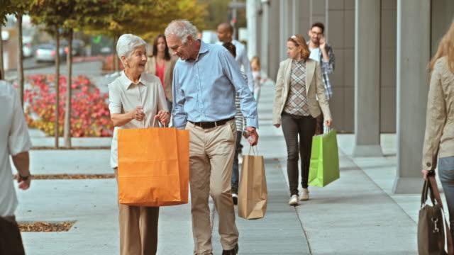 SLO MO of two seniors walking down the shopping alley video