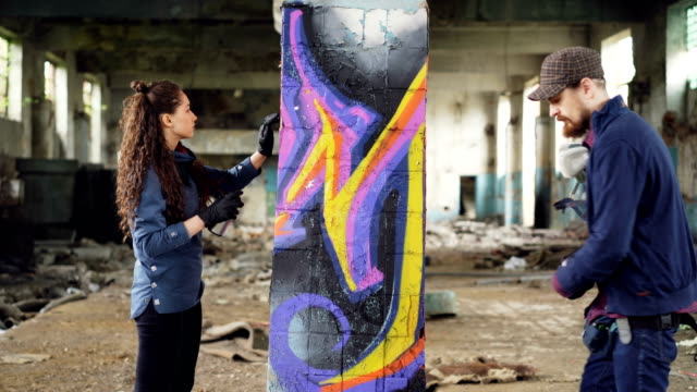 Two serious graffiti painters are decorating empty industrial building with abstract images using bright aerosol paint. Creative teamwork, young people and art concept.