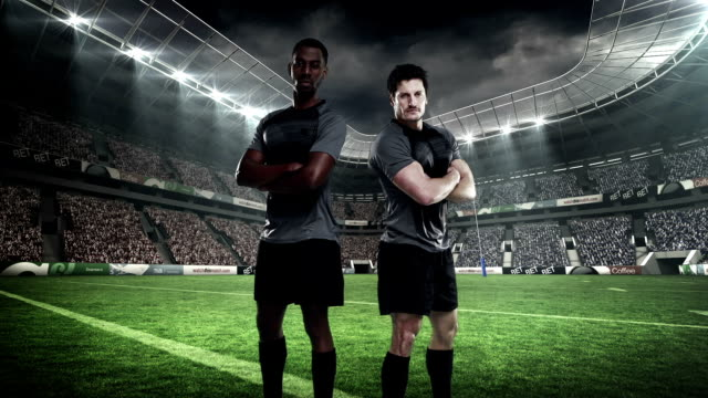 Two serious rugby players posing Two serious rugby players posing in stadium arms akimbo stock videos & royalty-free footage