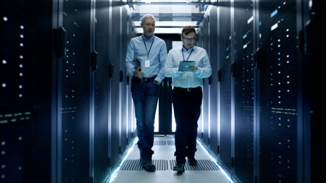 vídeos de stock e filmes b-roll de two server technician working in data center. one uses tablet computer. they walk through rows of server racks. - funcionamento em rede