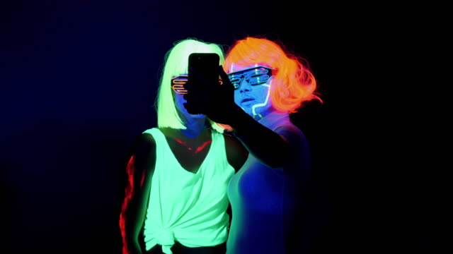 Two sexy cyber glow raver women filmed in fluorescent clothing under UV black light and using smartphone women taking selfies