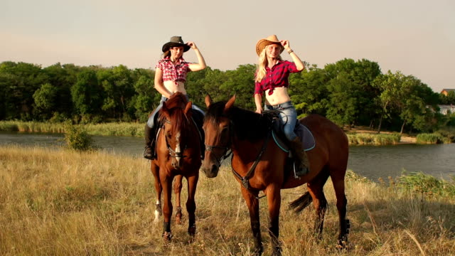 two sexy girls riding horses at sunset in a field. - cowgirl video stock e b–roll