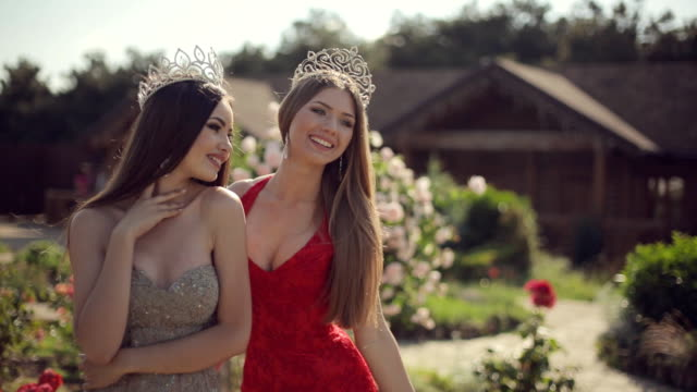 two sexy young female in the long gowns and crowns smiling and posing in the park with roses - prom fashion stock videos and b-roll footage