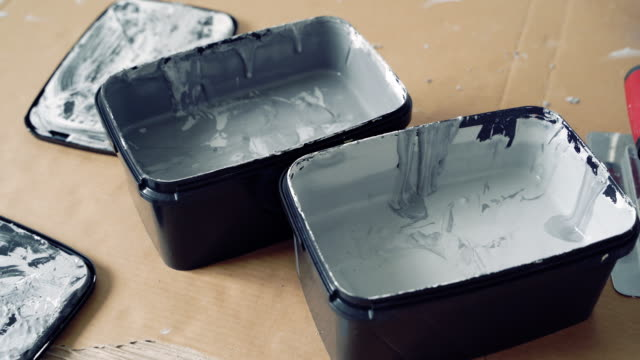 Two shades of grey decorative plaster or paint and spatulas on cardboard.