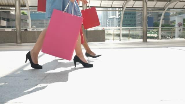 två shopaholics kvinna promenader med shopping väska - köpnarkoman bildbanksvideor och videomaterial från bakom kulisserna