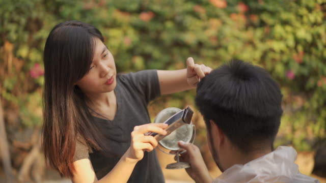 vídeos de stock e filmes b-roll de two short of asian quarantine couples cutting hair by clipper at home in covid-19 corona virus situation - covid hair