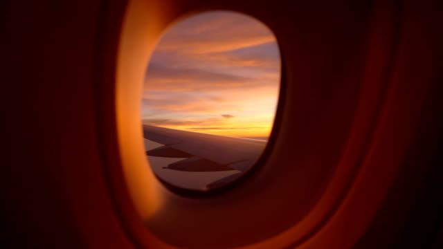 두 샷 아침에 아름다운 화려한 하늘과 비행기의 창을 찾고 - 항공기시점 스톡 비디오 및 b-롤 화면