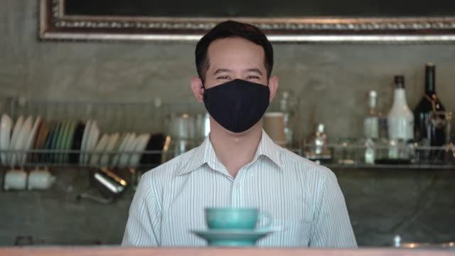 兩張亞洲男性咖啡師供應熱飲和微笑背後的面具 - 三四十歲的人 個影片檔及 b 捲影像
