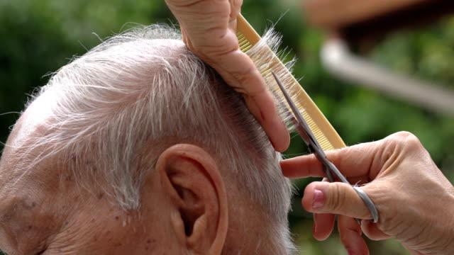two shots of asian senior having outdoor haircut - fryzura filmów i materiałów b-roll