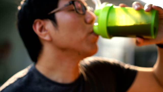stockvideo's en b-roll-footage met twee schoten van man weiproteïne drinken uit shaker fles blender - talk