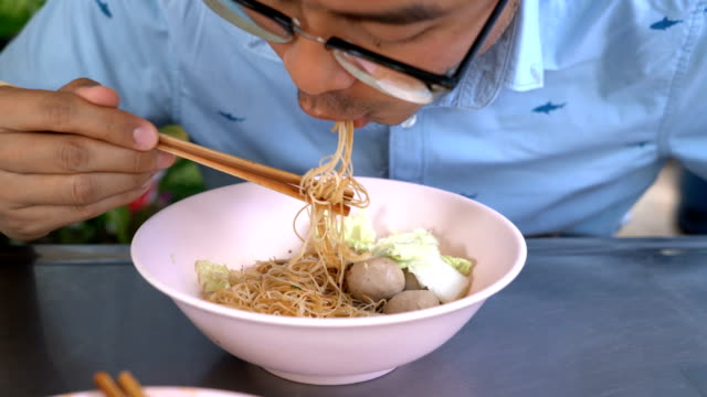 Two shots of man eating rice vermicelli noodle with pork ball